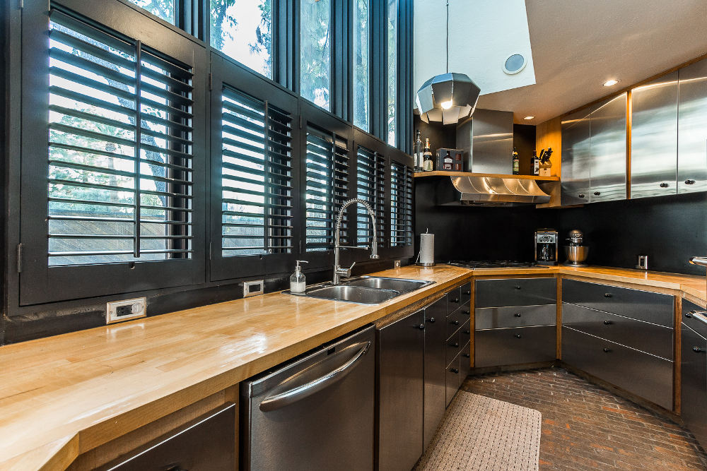 stainless-steel-kitchen-cabinets-phoenix-home-remodel-with-solid-wood-countertops-and-dark-colored-paint-with-brick-flooring